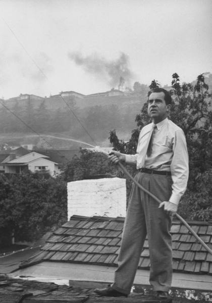 Senator Richard M. Nixon on roof of his home in Los Angeles, putting out fires caused by brush blaze.